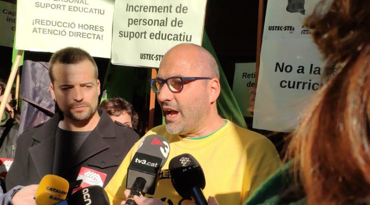 El portaveu de l'USTEC-STEs, amb altres professors, protesta davant la porta de la conselleria. USTEC-STEs