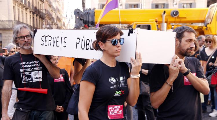 Una de les concentracions organitzada per la plataforma Aturem la Llei Aragonès, on els manifestants porten un taüt que simbolitza la mort dels serveis públics. Gerard Comas Robert (ACN)
