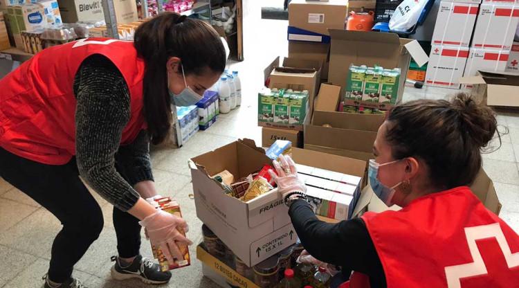 Uns voluntaris de la Creu Roja ajuden a fer paquets d'alimentació durant la pandèmia. Creu Roja Catalunya